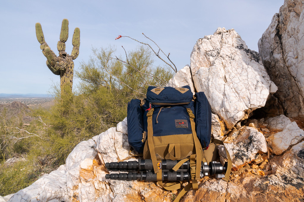 My Tom Bihn Guide's Pack backpack with my tripod underneath sits on quartz rocks on the Quartz Trail in McDowell Sonoran Preserve in Scottsdale, Arizona