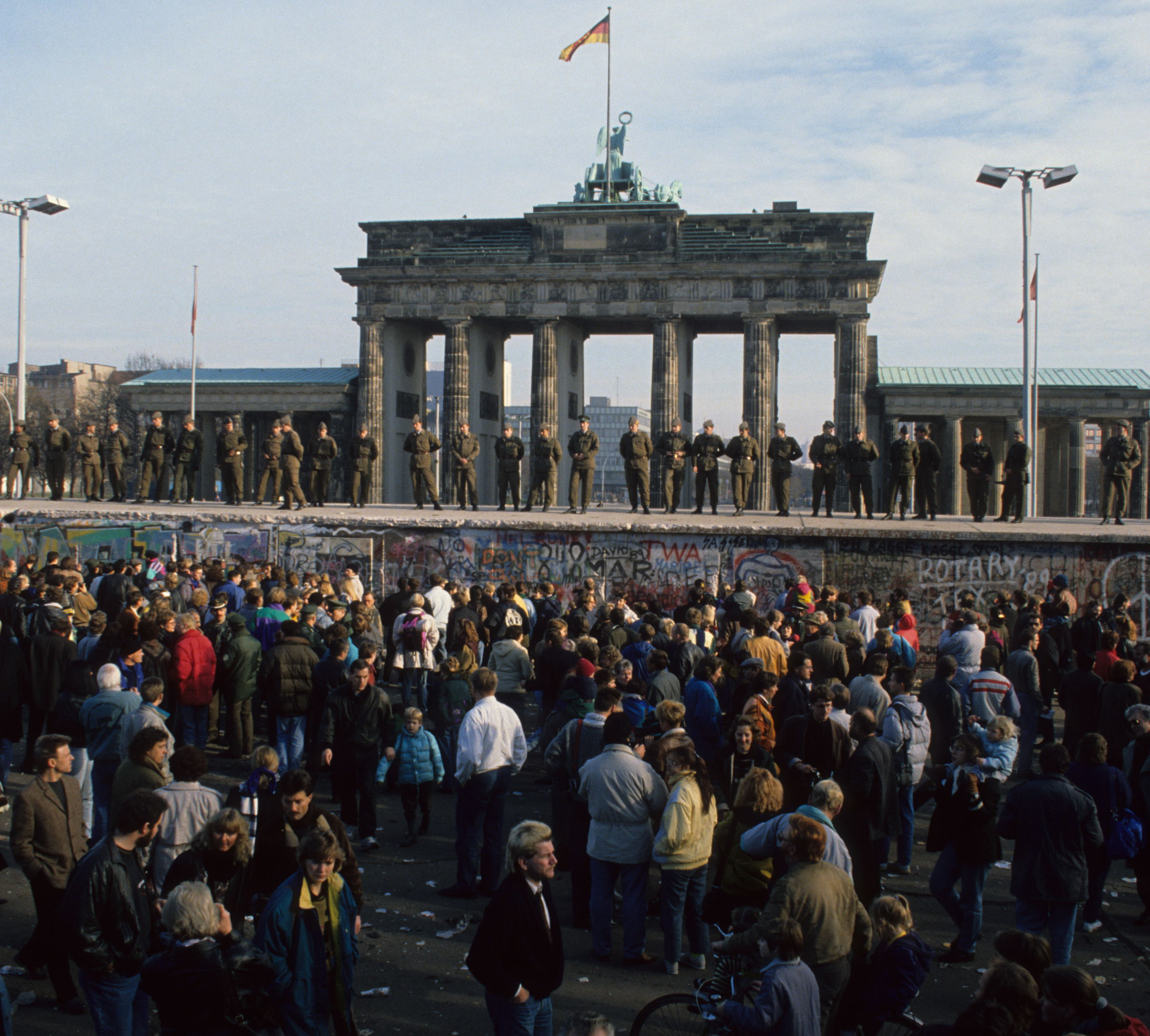 East German soldiers standing atop the Berlin Wall at Brandenburg Gate, November 1989. Photo courtesy of 25 Archiv Bundesstiftung Aufarbeitung – Uwe Gerig. (www.berlin.de/2013).