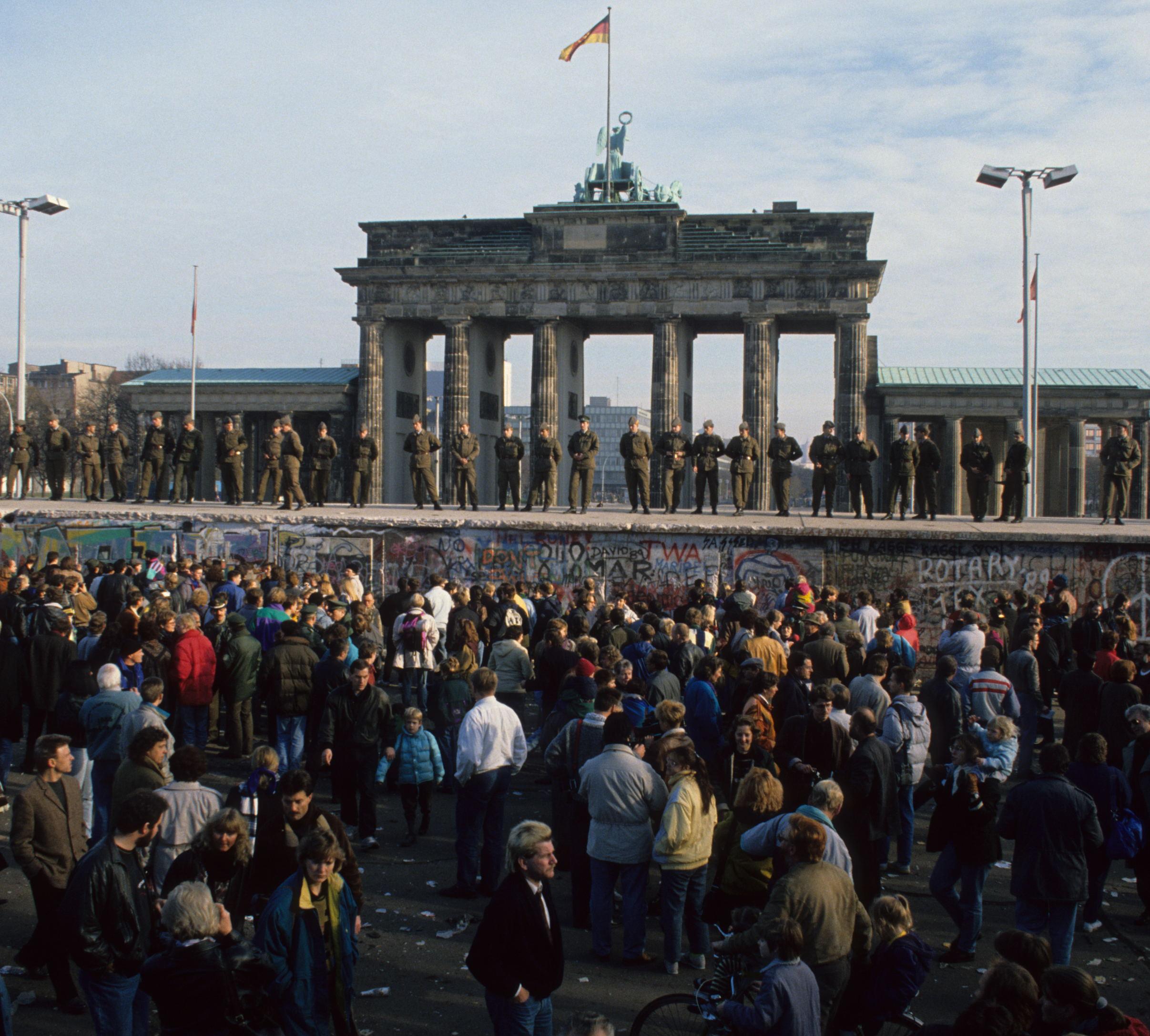East German soldiers standing atop the Berlin Wall at Brandenburg Gate, November 1989. Photo courtesy of 25 Archiv Bundesstiftung Aufarbeitung – Uwe Gerig. (www.berlin.de/2013).