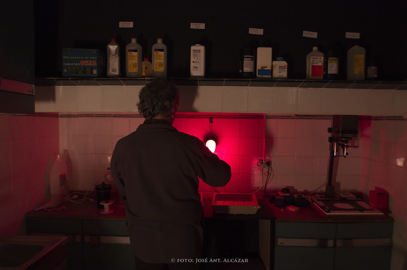 Persona de espaldas trabajando en un cuarto oscuro fotográfico