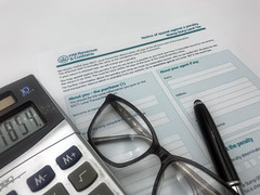A pen, some glasses, a calculator and a HMRC Stamp Land Duty Tax Form
