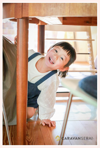 キッチンテーブルの下に潜り込む女の子