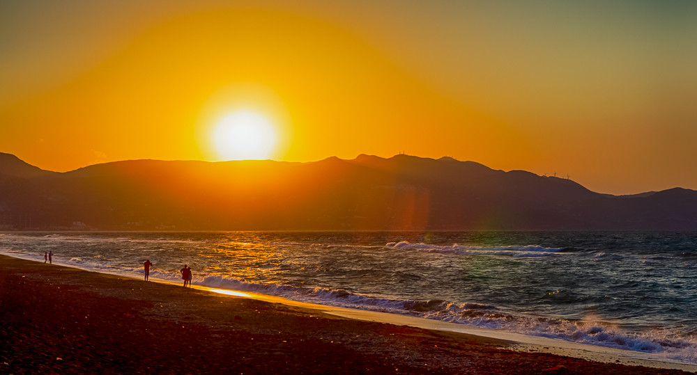 Amazing Picturesque Sunset on Heraklion Beach on Crete Island in Greece. Silhouettes Of People Wakling Along The Seashore