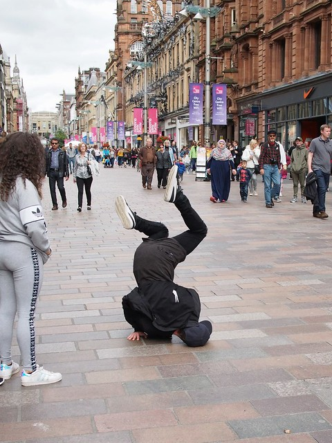 Breakdancer all in black balancing on head and hands in a city pedestrian mall; girl in a grey tracksuit standing nearby