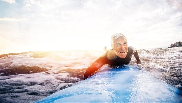 An elderly man surfing