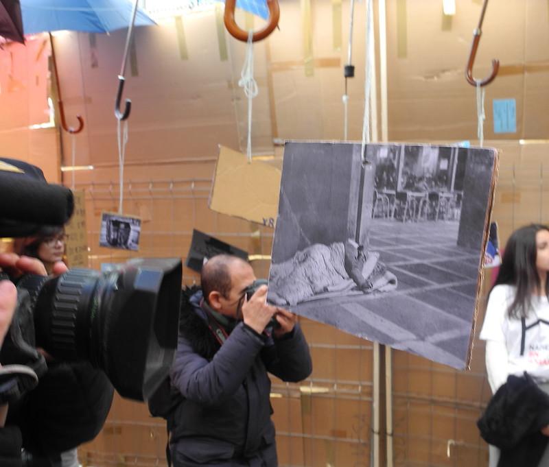 Unos reporteros haciendo fotos en un recinto con paraguas colgados del techo y una foto de un