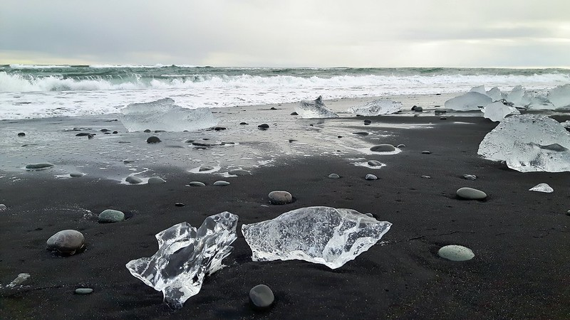 Glistening chunks of ice on a black sand beach in Iceland, Diamond Beach.