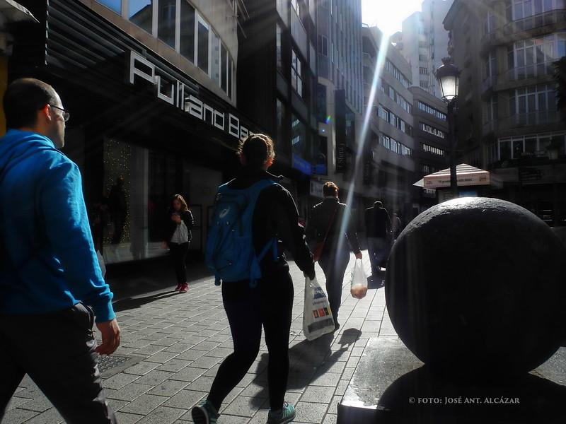 Personas caminando a contra luz en una calle peatonal.