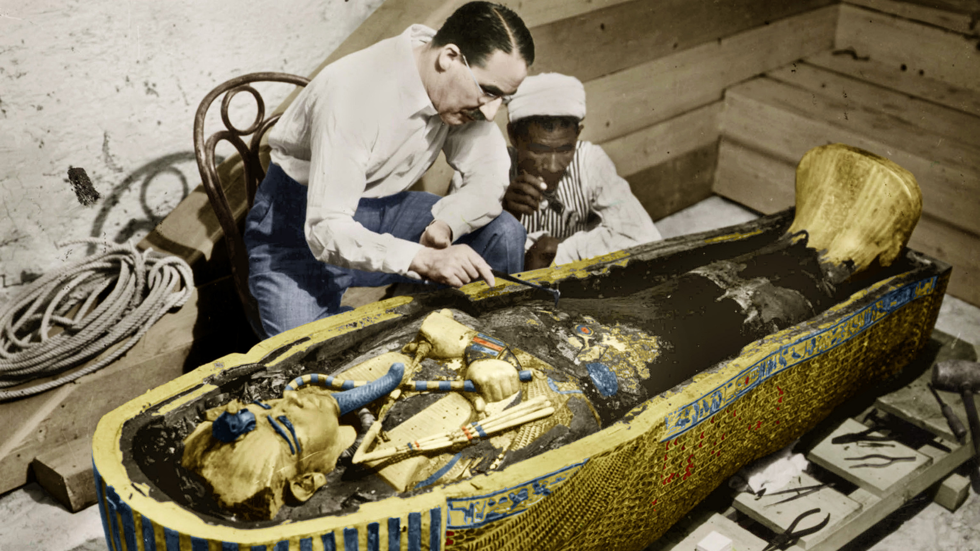 Howard Carter and an Egyptian worker examine the sarcophagus of King Tutankhamun, circa February 1923.
