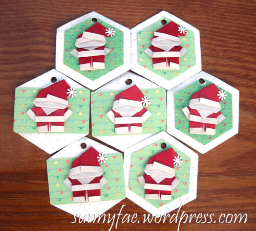 a group of origami santa tags