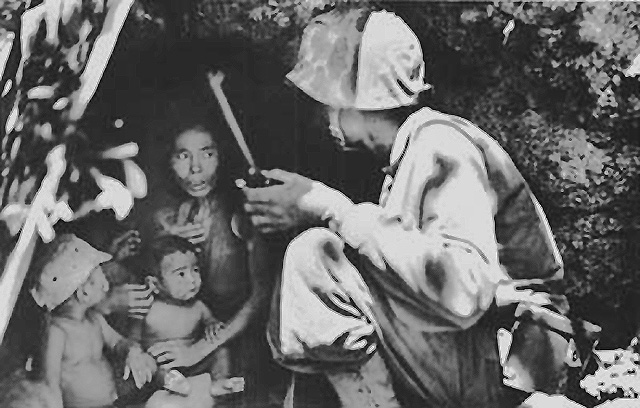 A United States Marine talks a terrified Chamorro woman and her children into leaving her refuge, photographed by Cpl. Angus Robertson USMC, circa June 21, 1944. The Marine pictured in this image is Lt. Robert B. Sheeks, who served as an Intelligence and Japanese Language Officer throughout the Pacific campaigns. More about him and his wartime experience can be read about in the book,