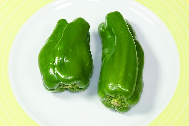 Bell Pepper_(2018_12_15)_2_resized_1 皿に置かれた2個の緑色のピーマンを撮影した写真。 頭を下向きにして置かれている。