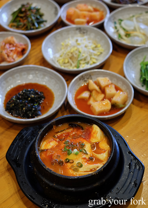 Spicy soft tofu stew with banchan at Myeong Dong Korean Restaurant in North Strathfield
