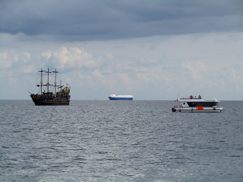 Pirate ship and small cruise boat heading towards Sopot's Pier in Poland