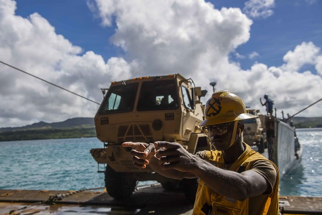 GUAM (Nov. 17, 2018) Boatswain's Mate 3rd Class Nayyaamunhotep Stubbs signals a 10-ton dump truck from the 9th Mission Support Command, 411th Engineer Brigade, Guam Army National Guard to drive inside the well deck of the amphibious dock landing ship USS Ashland (LSD 48) to transfer the equipment to the island of Saipan for Defense Support to Civil Authorities (DSCA) efforts. Sailors and Marines from Ashland, assigned to Commander, Amphibious Squadron 11, are providing Department of Defense support to the Commonwealth of the Northern Mariana Islandsâ civil and local officials as part of the FEMA-supported Typhoon Yutu recovery efforts. (U.S. Navy photo by Mass Communication Specialist 2nd Class Joshua Mortensen)