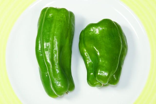 Bell Pepper_(2018_12_15)_1_resized_1 皿に置かれた2個の緑色のピーマンを撮影した写真。 頭を上向きにして置かれている。
