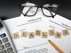Tax return deadline day 2019, amid tax return forms, glasses and a calculator