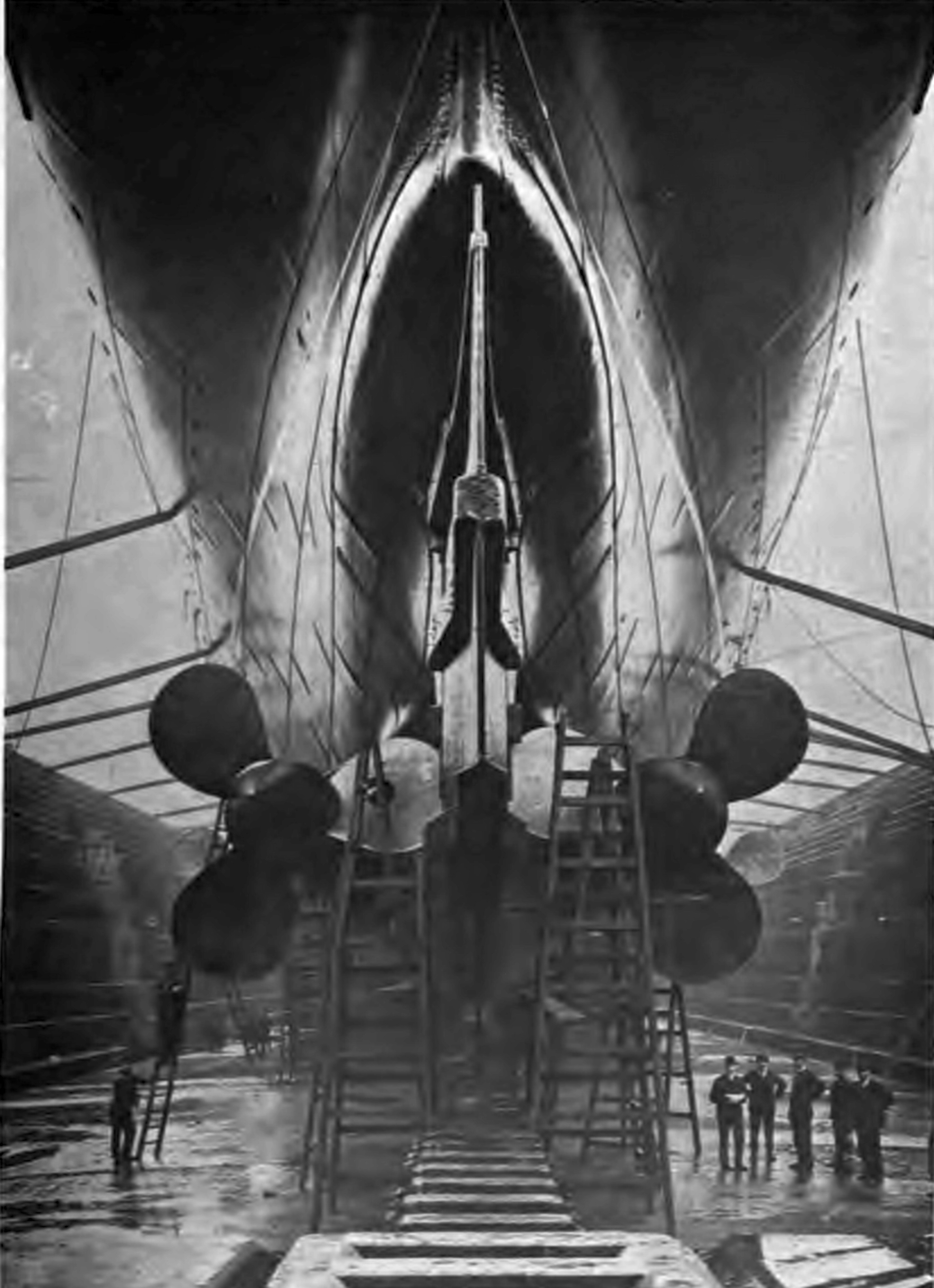 Workmen standing below Mauretania's original three-bladed propellers in dry dock