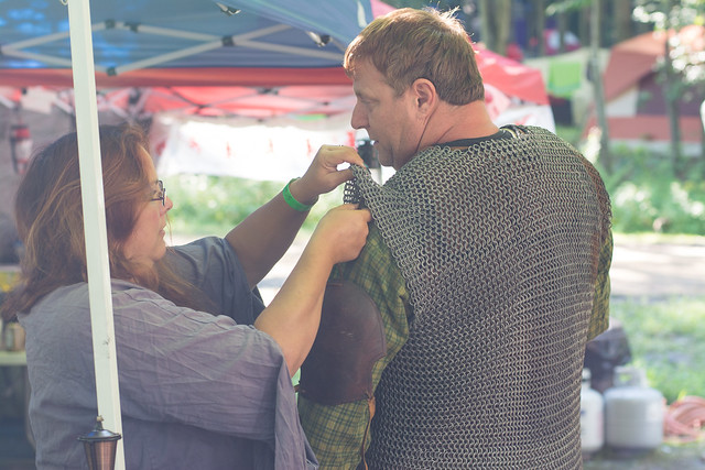 a woman adjusts the shoulder armor of a man in chain mail