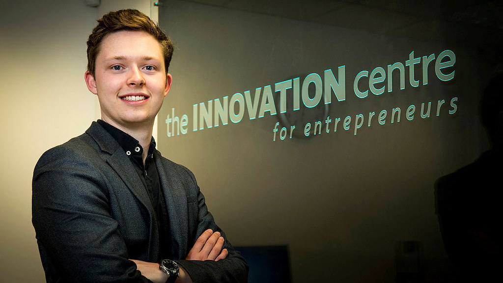 A young man in a suit in front of a sign that says 'Innovation Centre'