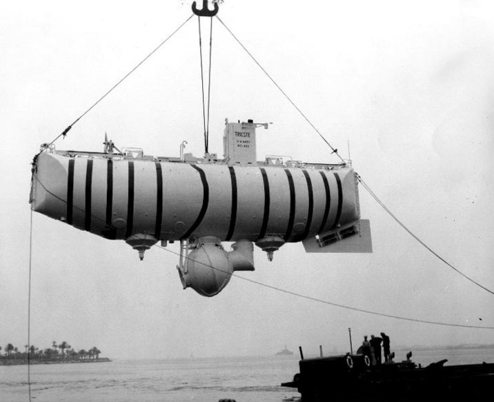 USS Trieste is hoisted out of the water in a tropical port, circa 1958-59, soon after her purchase by the U.S. Navy. Retrieved from NH 96801 U.S. Navy Bathyscaphe Trieste (1958-1963), Art collection, U.S. Naval History and Heritage Command website. Released by the U.S. Navy Electronics Laboratory, San Diego, California.