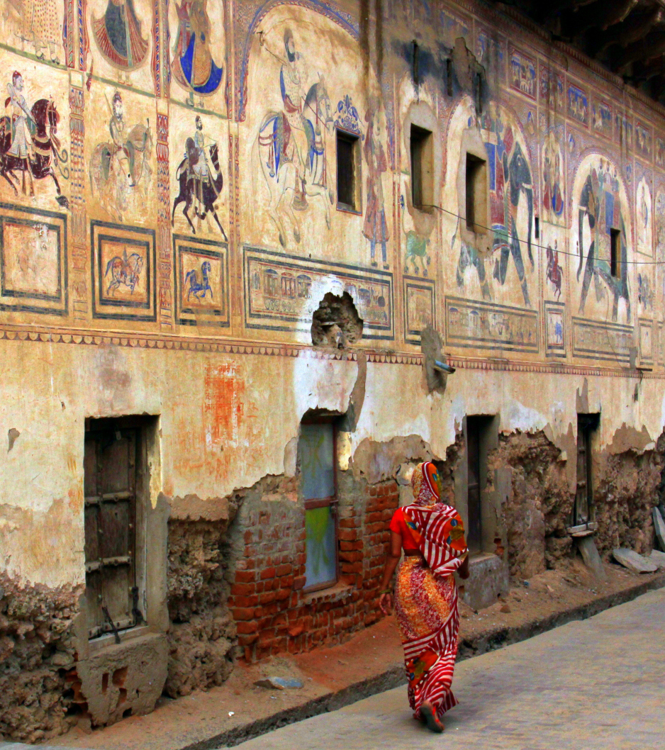 a woman walks past a painted haveli in shekhawati