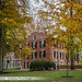 Wilson Hall on College Green through trees in fall