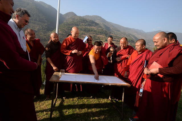 A Cal Poly professor and a group of monks outside in the mountains looking at a piece of paper on a table.