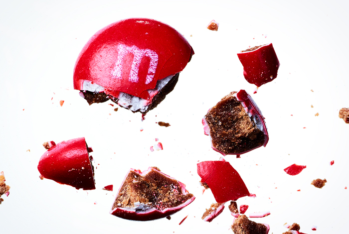 Close-up of a red M&M broken into several pieces.