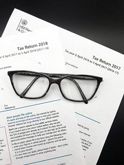 2 tax return forms, a 2018 tax return form and 2017 tax return form and black glasses.