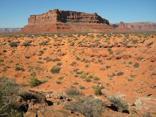 A red sandstone butte with sage brush in front at the Valley of the Gods in Utah, USA
