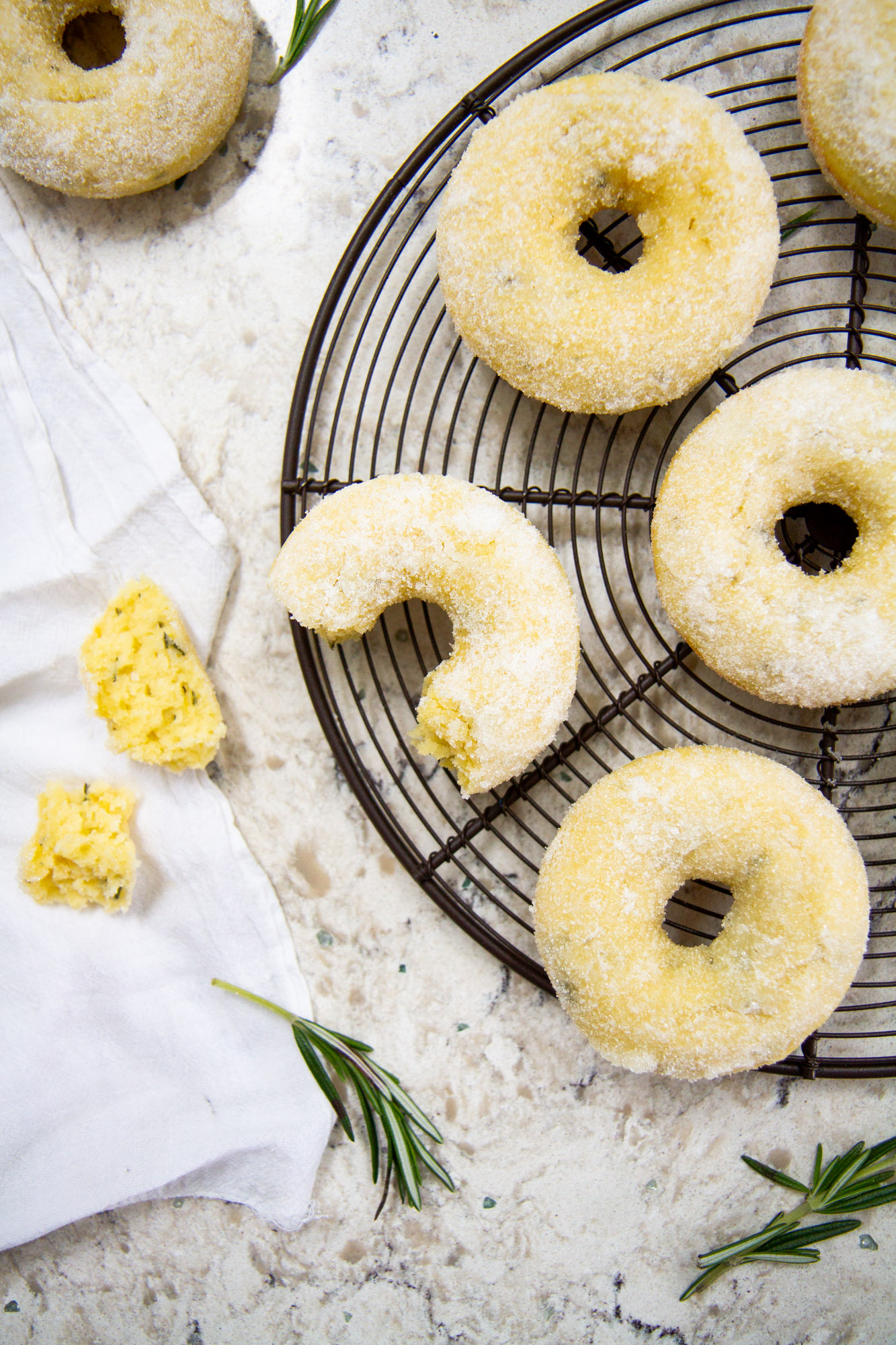 Lemon-Rosemary Olive Oil Cake Donuts -- A deliciously moist and tender baked donut recipe flavored with fresh lemon, rosemary, and olive oil and tossed in sugar. @girlversusdough #girlversusdough #doughnuts #breakfast
