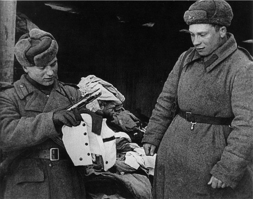 Red Army soldiers examining child clothing at Auschwitz, January 1945